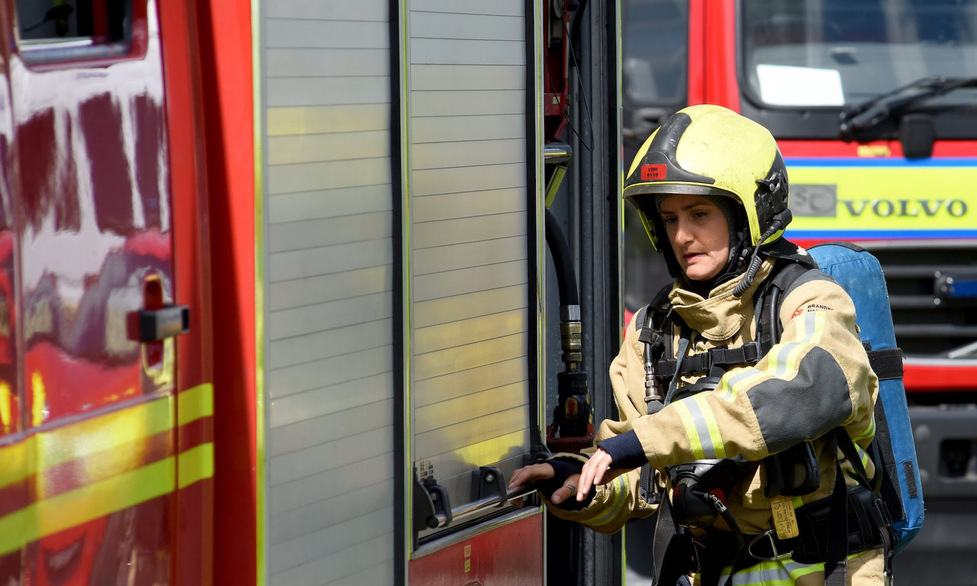 Firefighter opening the fire compartment on a fire appliance