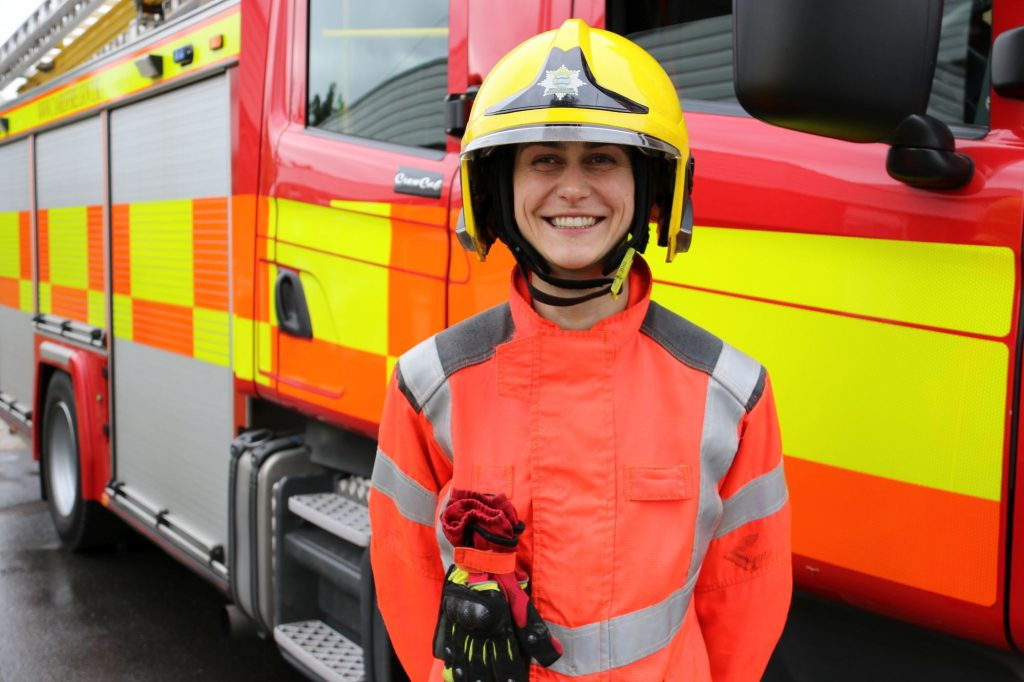 Firefighter Agata standing in front of the a fire appliance in her uniform